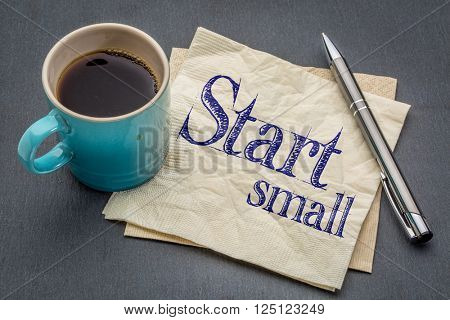 start small advice - handwriting on a napkin with cup of coffee against gray slate stone background