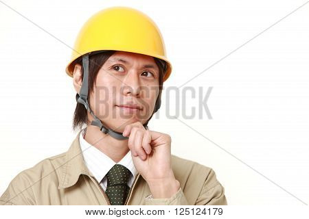young Japanese construction worker thinks about something