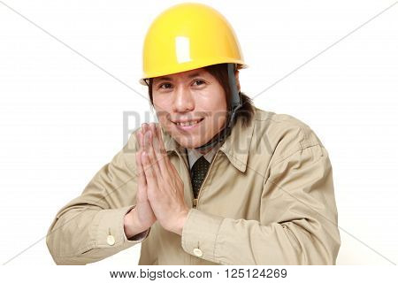 construction worker folding his hands in prayer