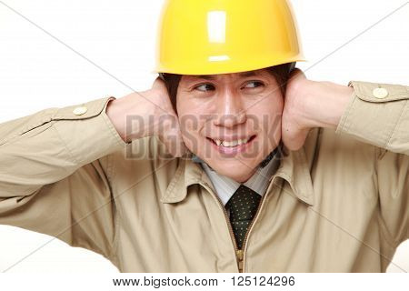 Young Japanese construction worker suffers from noise