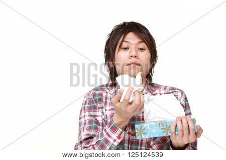 young man with an allergy sneezing into tissue