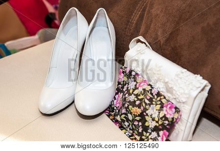 white shoes of the bride and beige sofa