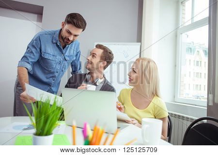 Attractive young man is consulting with his colleagues about his project. He is standing and showing a document. The man and woman are sitting at desk and smiling