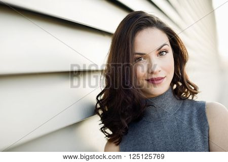 Beautiful young woman model of fashion smiling in urban background
