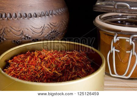 Strands of saffron and saffron powder on a wooden table