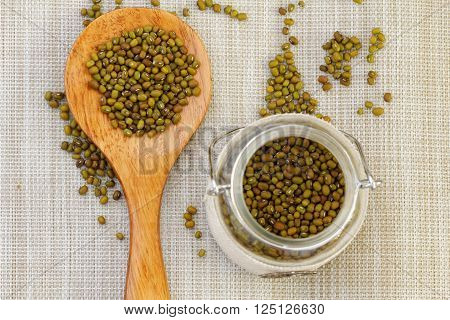 Mung beans in wooden spoon and glass jar