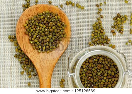 Mung beans in wooden spoon and glass jar. Selective focus.