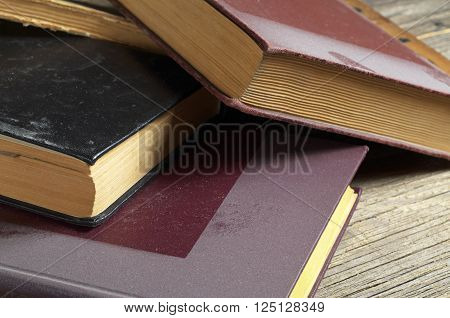 Old books covered with dust on wooden table