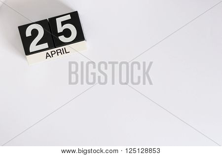 April 25th. International Day of DNA. Image of april 25 wooden color calendar on white background.  Spring day, empty space for text.