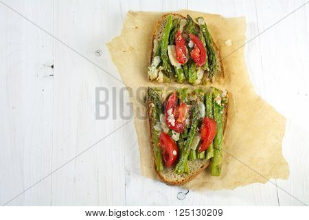 green asparagus tomatoes and parmesan gratinated on toasted bread fresh out of the oven baking paper on a white painted wooden background with copy space view from above
