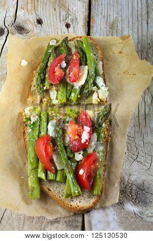 spring toast roasted bread with green asparagus tomatoes and parmesan gratinated on baking paper and a weathered rustic wooden background view from above vertical