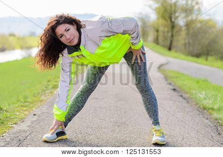 Sporty attractive young woman doing stretching exercises while looking up at the camera on a rural pathway wearing a high visibility jacket