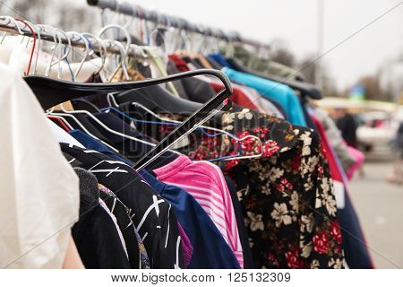 second hand clothes hanging on a rack for sale at a flea market selected focus