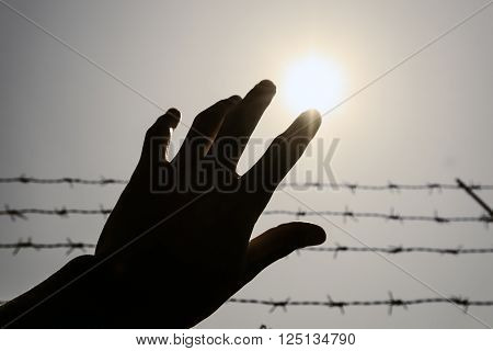 Silhouette hand extending to the sky with barbwire and sunlight , vintage tone