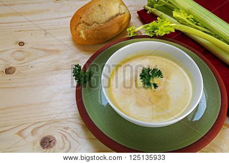 vegetable cream soup with celery and parsley garnish in a bowl on a green plate, wooden background with copy space