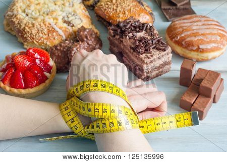 Addiction to sweets concept with woman's hand and centimeter