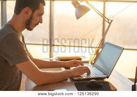 Young business man working on a laptop at his desk in the office, in view of the profile against the window