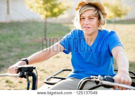 Boy riding farm truck in vineyard