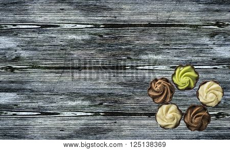 Much chocolate cakes with cream on wooden background