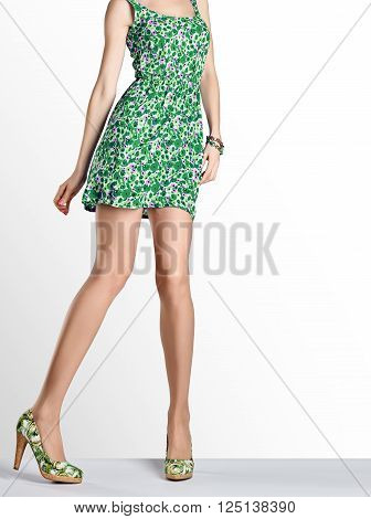 Woman in fashion vintage dress and high heels. Perfect female sexy long legs, stylish green flower sundress and summer glamour shoes. Unusual creative elegant walking out outfit, people. Copy space