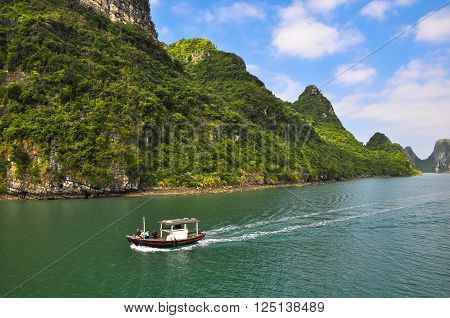 December 18, 2013, Halong Bay, Northern Vietnam. People in a motor boat sailing among the islands in the bay. ** Note: Visible grain at 100%, best at smaller sizes