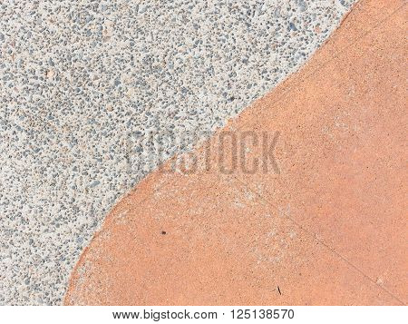 Old gray concrete surface with depressed gravel and red decorative concrete surface and smooth line between on the track in the street