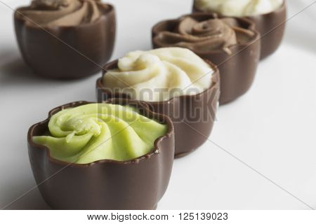Much chocolate cakes with cream on white background