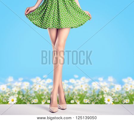 Woman long legs in fashion dress and high heels. Perfect female  sexy legs in stylish green skirt and summer glamour shoes on flower chamomile field. Unusual creative elegant walking out outfit, people