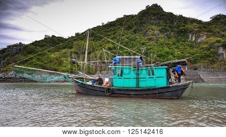 December 15 2013. Fisherman and his family is sailing in a traditional Vietnamese fishing boats among the islands of Halong Bay Northern Vietnam.