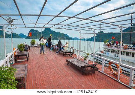 December 15 2013. Tourists from the open top deck of the ship admiring the magnificent scenery of Halong Bay. North Vietnam.