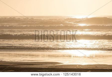 A setting sun splashes golden light on a Pacific Coast beach glistening off the waves crashing onto the sand