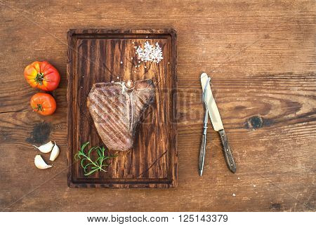 Cooked meat t-bone steak on serving board with garlic cloves, tomatoes, rosemary and spices over rustic wooden background, top view, copy space