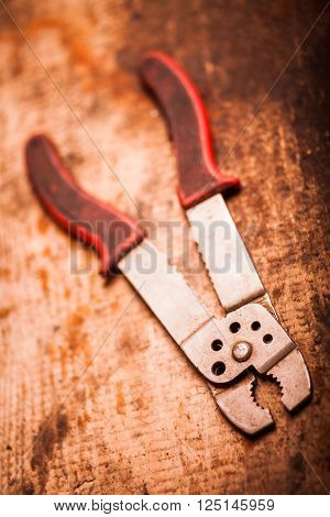 Color image of a wire stripper on a wooden plank.
