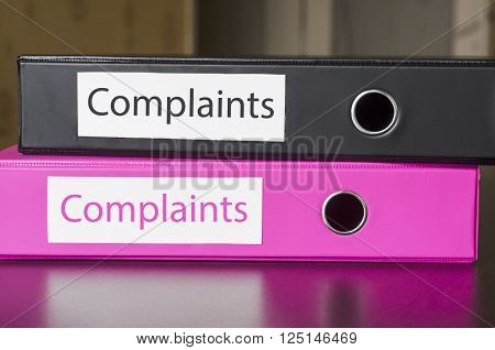 Bright office folders over dark background and complaints text concept
