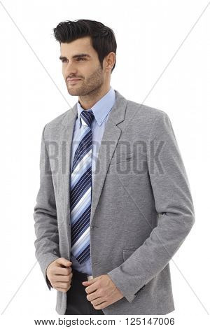 Young businessman in suit and tie looking away.