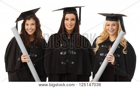 Portrait of three attractive female graduates smiling happy in academic dress, holding diploma.