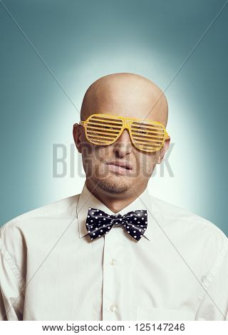 Bald man in fashion glasses and in white shirt with bow-tie
