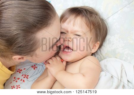 Dad kissing little baby daughter and ticking her with mustache