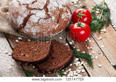 Closeup photo of rustic floured bread, two pieces of bread, dill, two tomatoes and oat flakes on sackcloth on planked wooden table