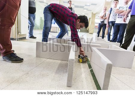 Sofia, Bulgaria - April 5, 2016: A student is helping his self-made robot in a labyrinth during an open competition among school students.