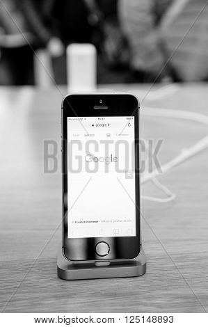 STRASBOURG FRANCE - APR 9 2016: New iPhone SE in docking station with Google search engine page opened. New Apple iPhone tends to become one of the most popular smart phones in the world.