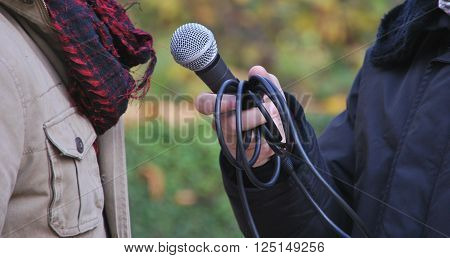 Man talking to a journalist with micro outdoor. Unrecognizable. Bokeh