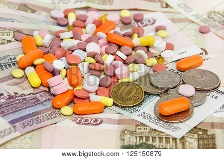 Many different tablets on the background of Russian money. Prices of medicines