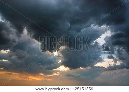 heavy cumulus before storm over amber horizon