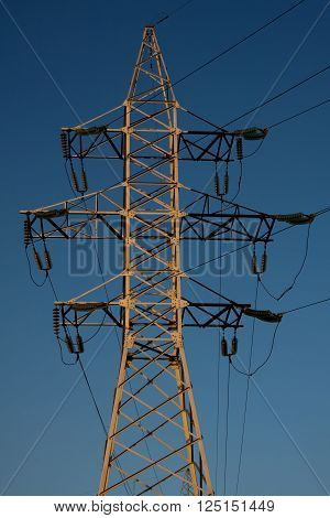 metal support, power lines on background of blue sky. Electrification.