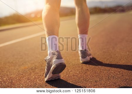 Running sport shoes on runner. Legs and running shoe closeup of man jogging outdoors on road.Selective focus