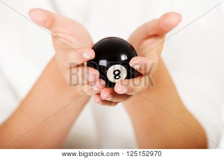 Businesswoman holding eight billiard ball