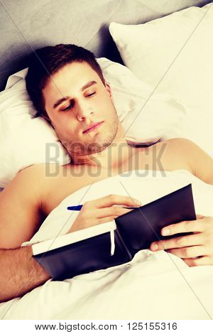 Man writing a note in his bed.