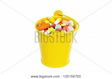 Many different pills in a yellow bucket on white background
