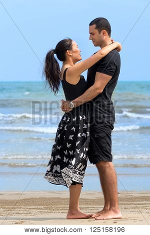 Romantic couple on beach.Young happy interracial couple looking to each other and smiling on beach. Asian womanCaucasian man